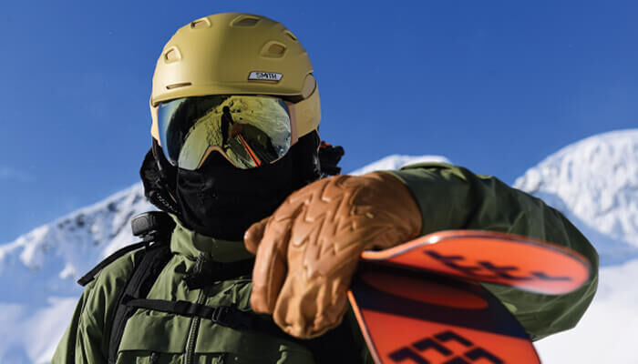 Man wearing Smith snow goggles and helmets on the mountain