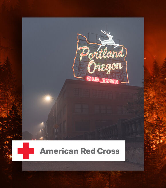 "American Red Cross logo over the famous ""Portland, OR"" sign obscured by heavy smoke."
